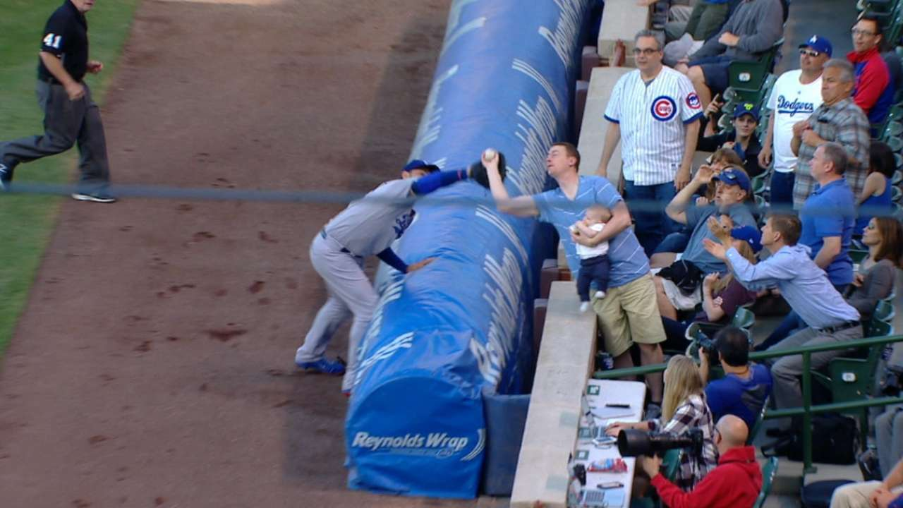 Oh baby, what a catch! Fan holds son, snags ball
