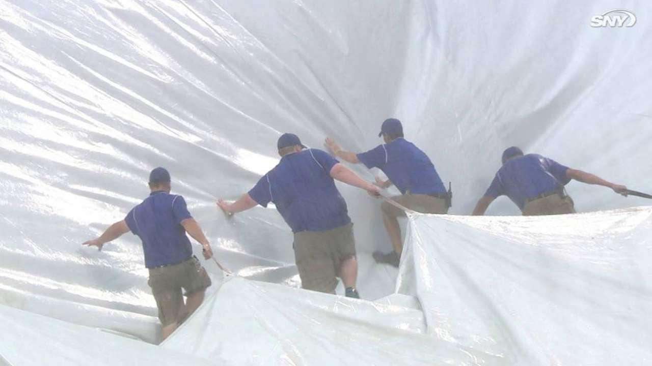 Grounds crew wrestles with tarp