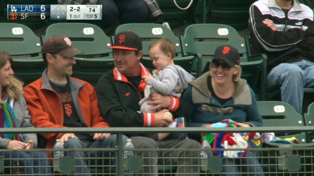 Fan catches ball holding baby