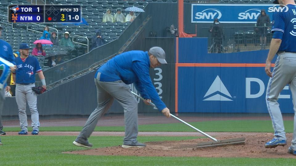 Grounds crew tends to wet field